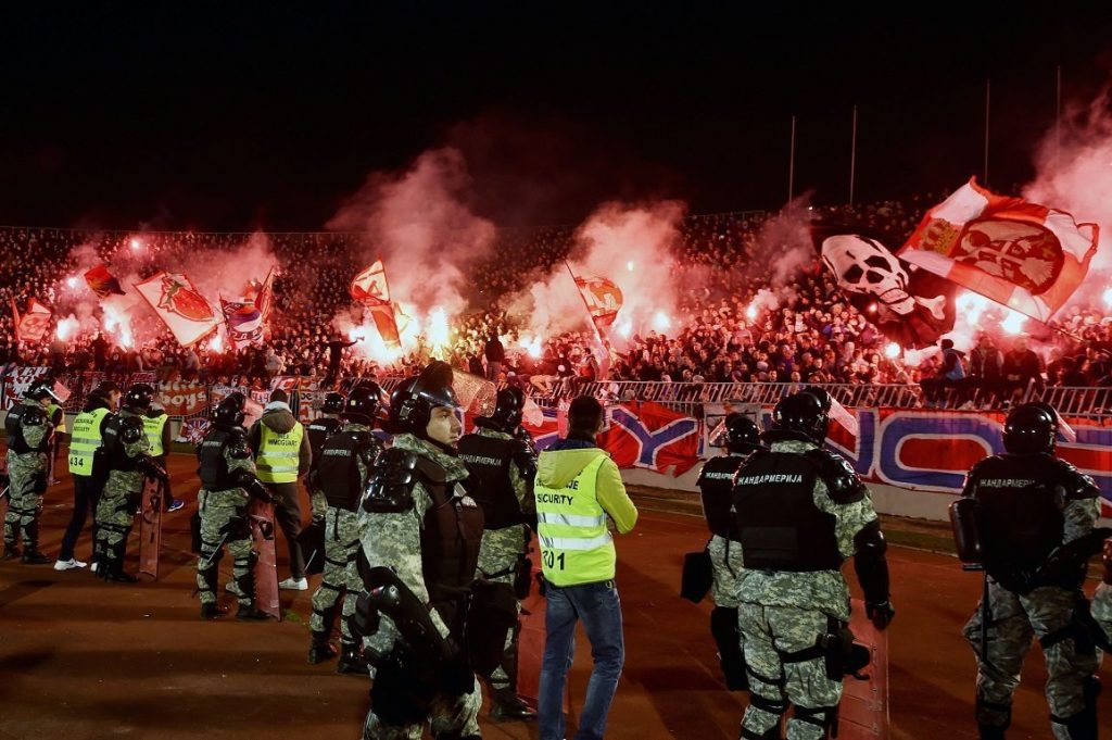Anti riot police officers stand guard as Red Star's supporters burn torches during the Serbian National soccer league derby match between Partizan and Red Star, in Belgrade on February 27, 2016. Red Star won 1-2 at the 150th edition of the 'Eternal Derby'.  / AFP / ANDREJ ISAKOVIC        (Photo credit should read ANDREJ ISAKOVIC/AFP/Getty Images)