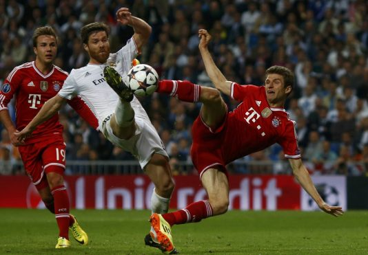 Real Madrid's Xabi Alonso kicks the ball in front of Bayern Munich's Mario Goetze (L) and Thomas Mueller (R) during their Champion's League semi-final first leg soccer match at Santiago Bernabeu stadium in Madrid, April 23, 2014.                REUTERS/Michael Dalder (SPAIN  - Tags: SPORT SOCCER TPX IMAGES OF THE DAY)